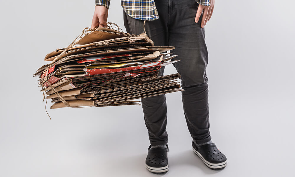 man holding bundle of flattened cardboard boxes tied up with string