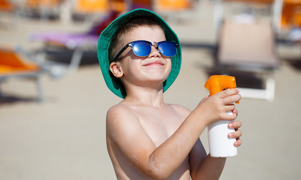 young shirtless boy wearing sunglasses holding spray sunscreen practicing sun safety