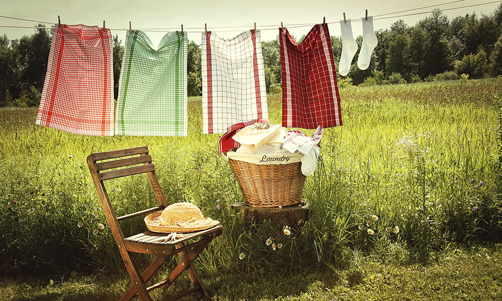 a cloths line outside with hanging towels and a chair and a small pile of laundry