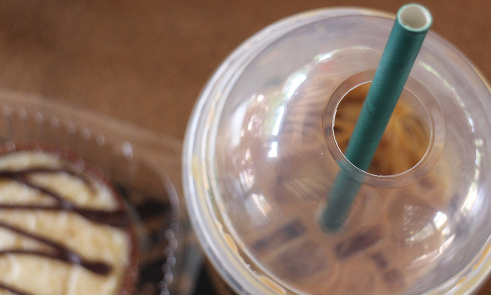 a closeup of an iced Starbucks beverage with one of their new cardboard straws
