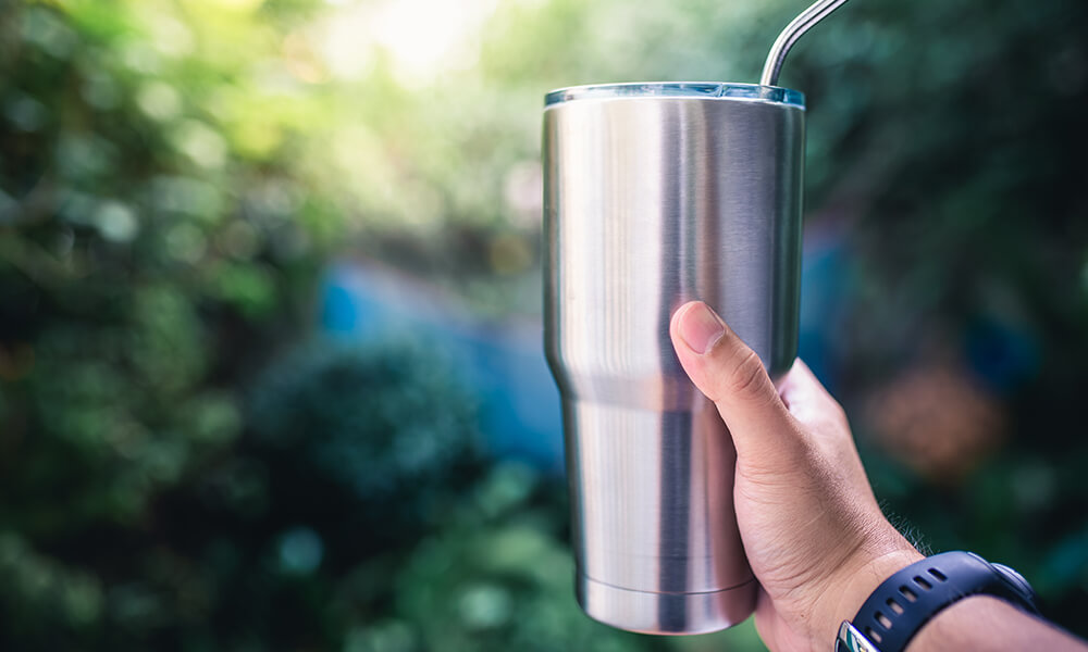 a hand holding a coffee tumbler with metal straw, a small change made to help make environmental impacts