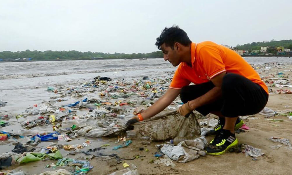 indian man cleaning up trash from the beach