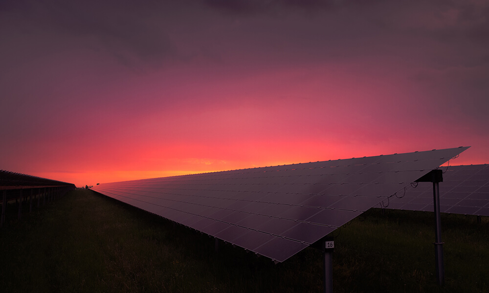 a dramatic photo of a solar panel at sunset with a pink sky
