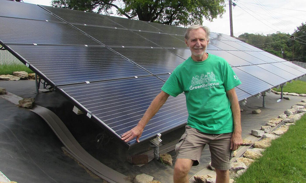 Don Priester posing in front of his solar panels